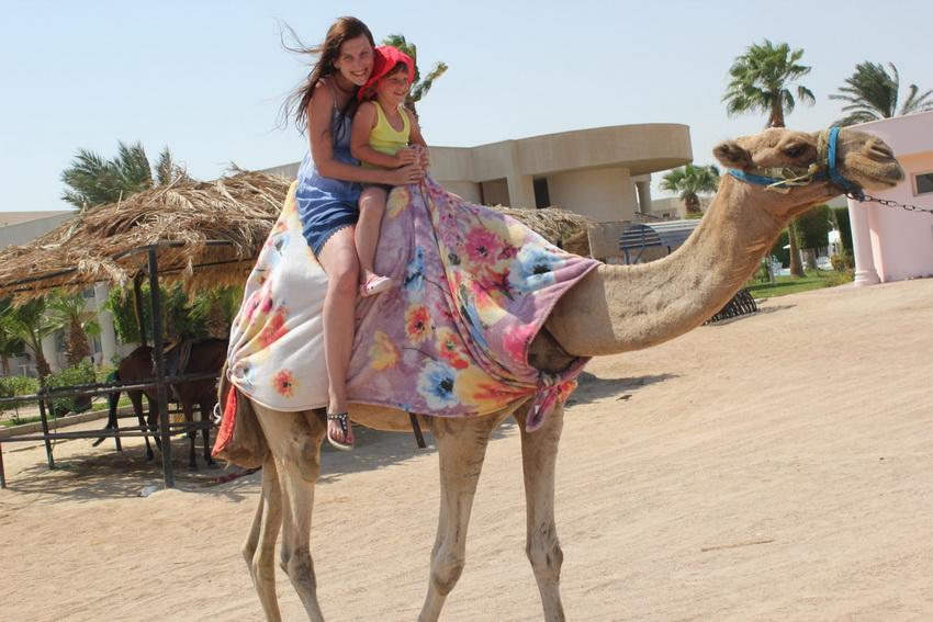 Мараниа с дочкой катаются на верблюде Сергее на пляже.