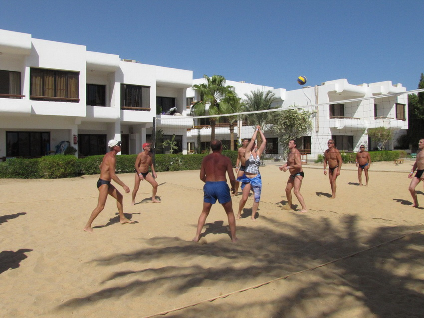 Туристы играют в пляжный волейбол.