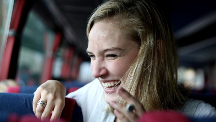 Девушка смеется в автобусе