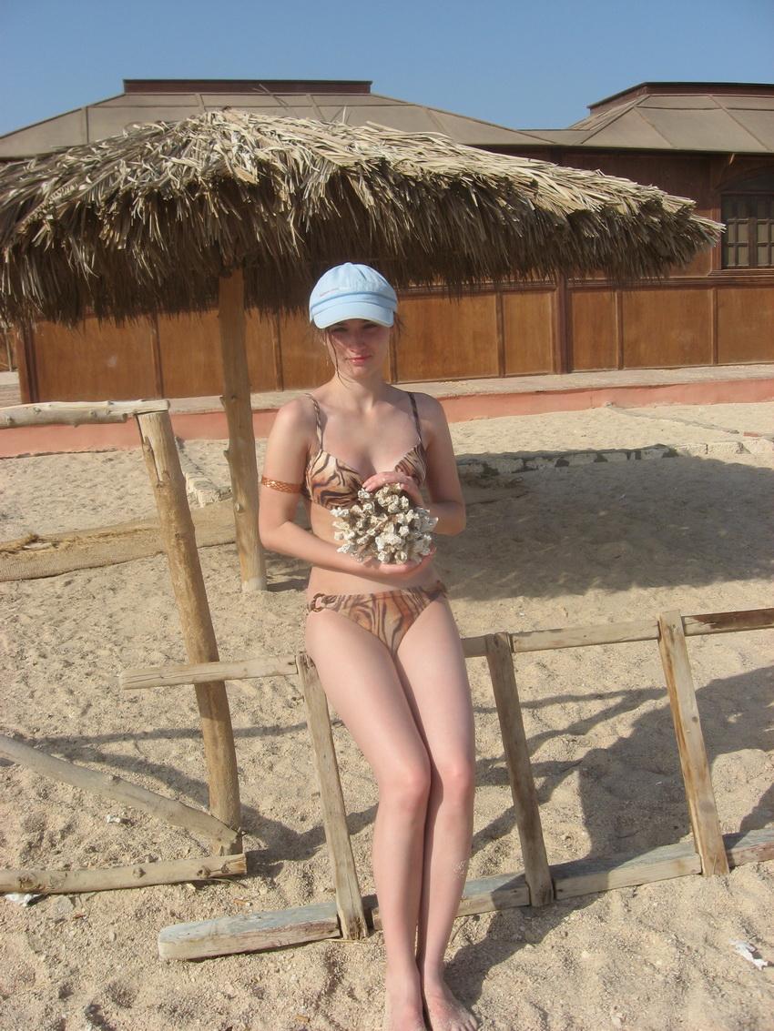 Песчаный пляж и коралл в руках.