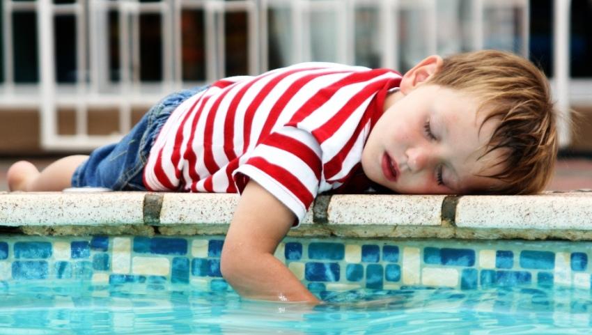 Грустный ребенок у бассейна.